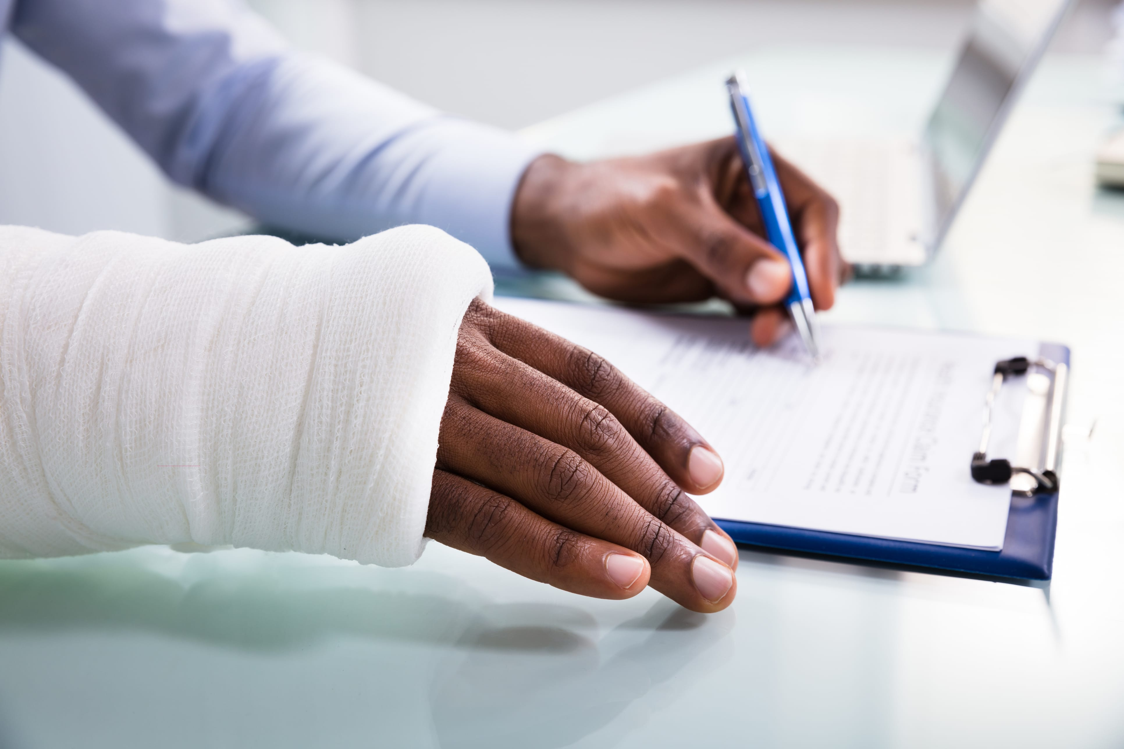 Injured Man Filling Insurance Claim Form