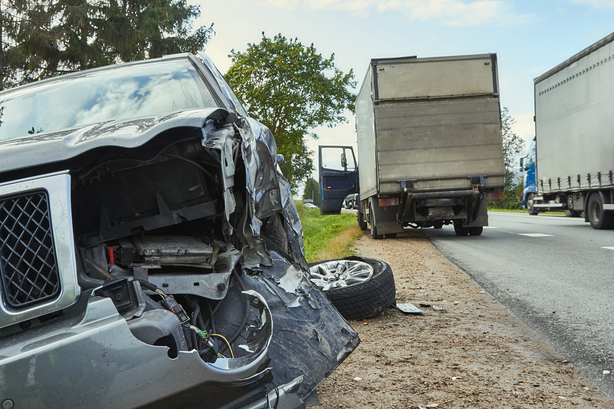 Car damaged after trucking accident involving two commercial trucks