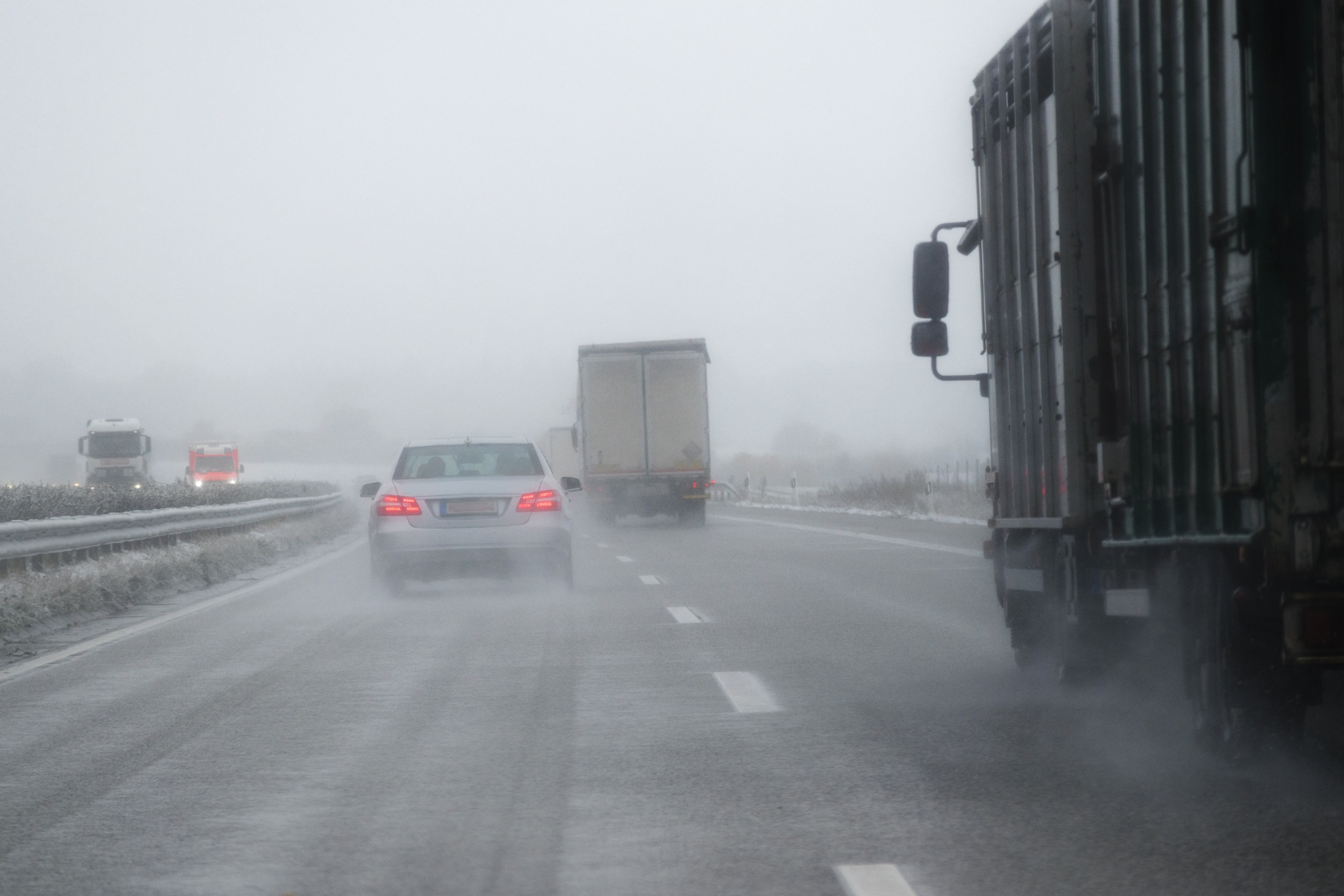 Cars and trucks driving on the highway in a snow storm