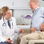 Doctor working with man experiencing pain from hip replacement.