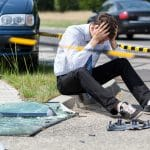Man sitting at the scene of an auto accident
