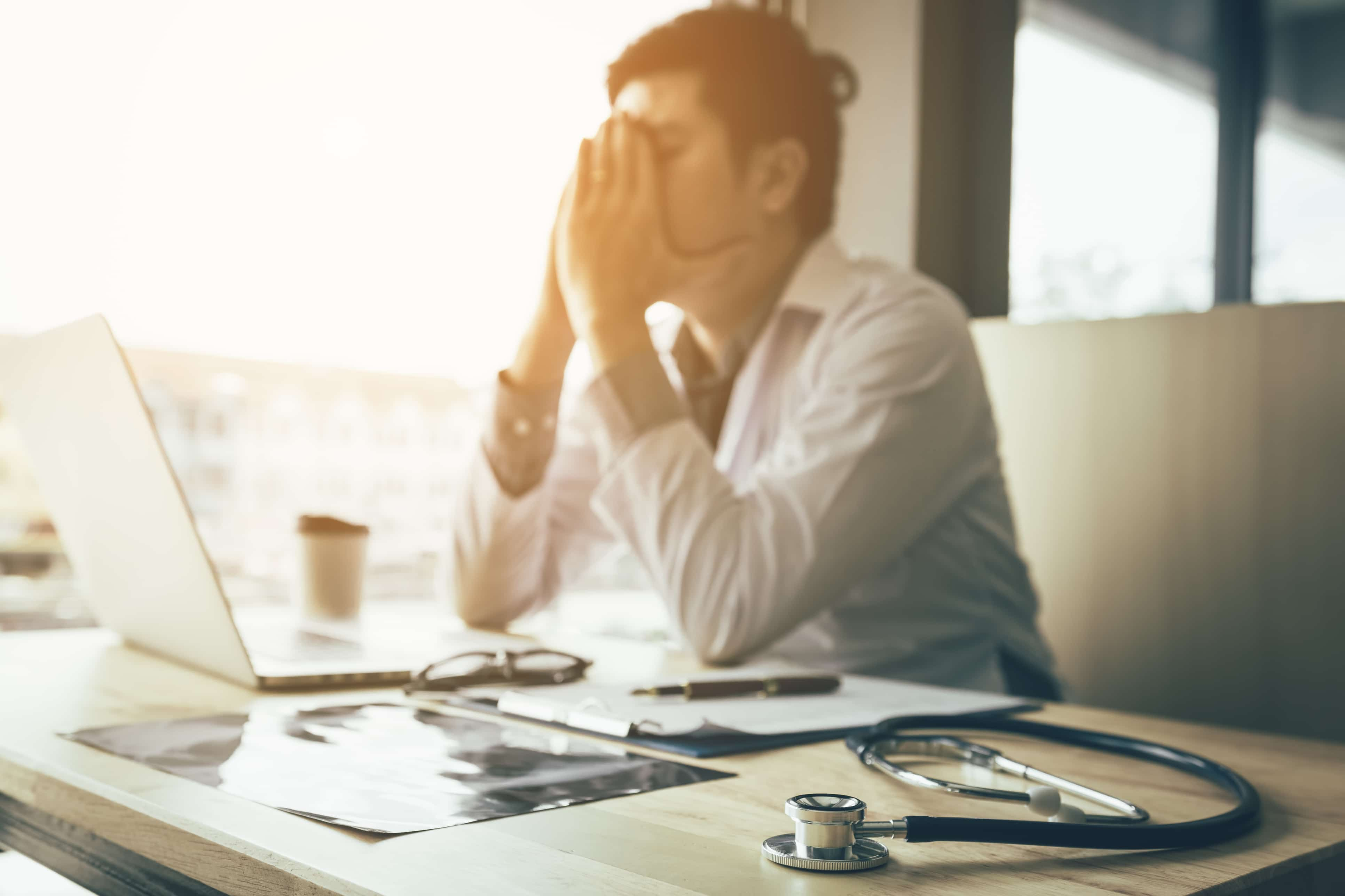 Emotional doctor sitting in office with hands covering his face.